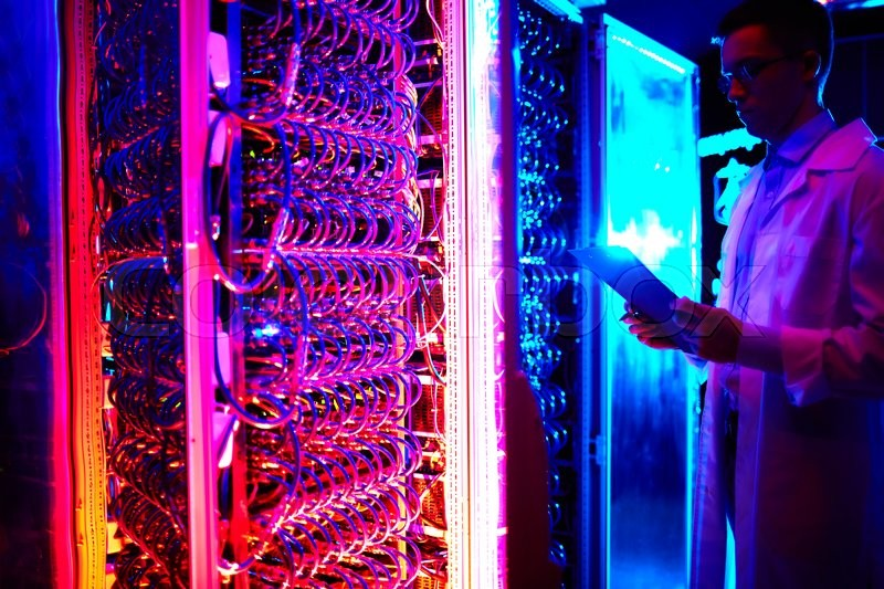 Young engineer working in data storage center, stock photo