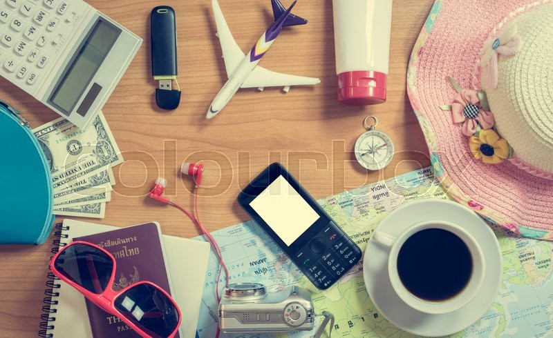 Set of travel accessory and cup of coffee on wooden vintage background, stock photo