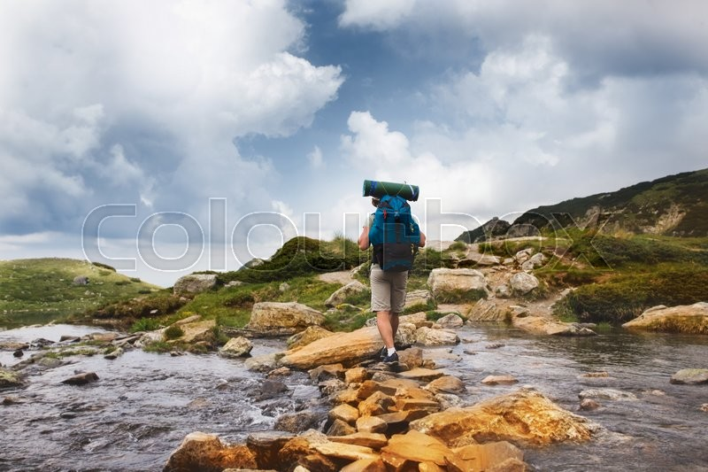 Hiker man with backpack crossing a river on stones in bulgarian mountains. Hiking and leisure theme. Image with sunlight effect, stock photo