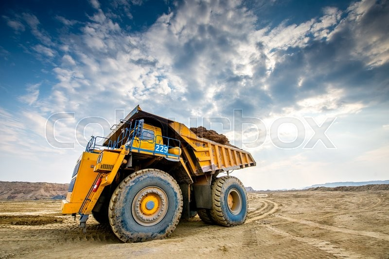 Big yellow mining truck ground moving in open pit, stock photo