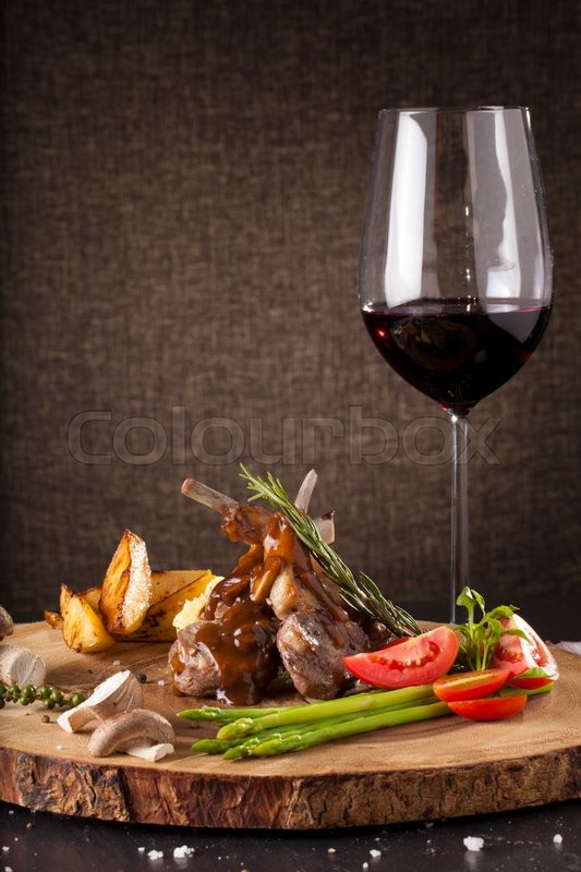 Rack ofRack of lamb steak cut in pieces decorate and seasoning with vegetable and herbs and red wine serve on chopping wood block lamb steak cut in pieces seasoning with crusted mint vegetable and herbs and red wine serve on chopping wood block, stock pho