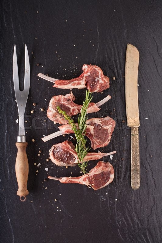 Raw rack of lamb cut in pieces decorate and seasoning with rosemary tomato herbs and olive oil fork and knife on black stone, stock photo