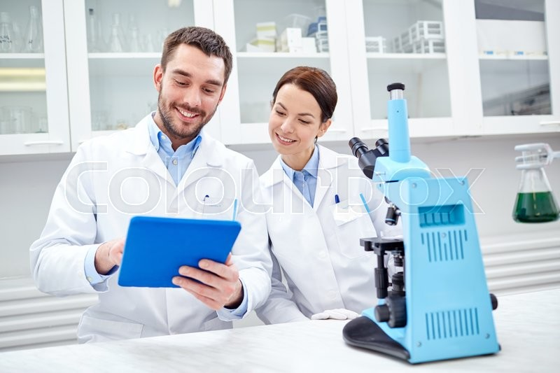 Science, chemistry, technology, biology and people concept - young scientists with tablet pc and microscope making test or research in clinical laboratory, stock photo