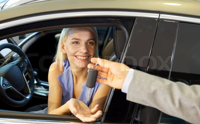 Auto business, car sale, consumerism and people concept - happy woman taking car key from dealer in auto show or salon, stock photo