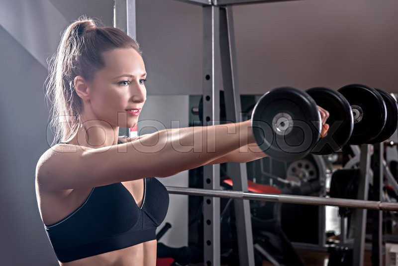 Strong woman weightlifting at the gym. Woman working out with dumbbells at a gym. Dumbbell bicep curl by a fitness girl. In good condition, stock photo