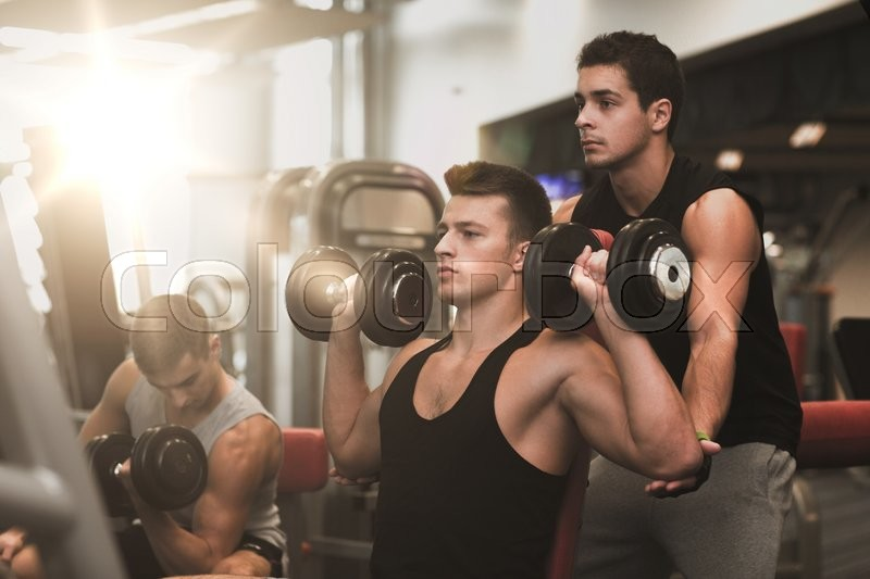 Sport, fitness, lifestyle and people concept - group of men with dumbbells in gym, stock photo