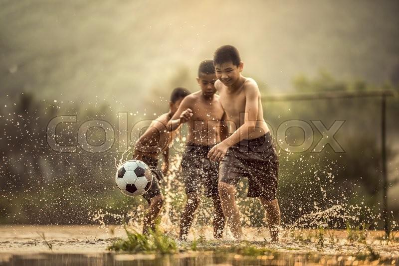 Boy kicking a soccer ball (Focus on soccer ball), stock photo