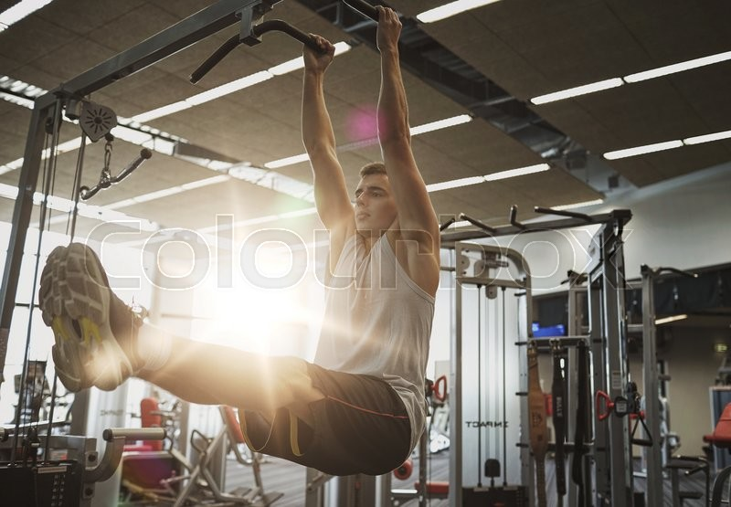 Sport, fitness, lifestyle and people concept - young man flexing abdominal muscles on pull-up bar in gym, stock photo