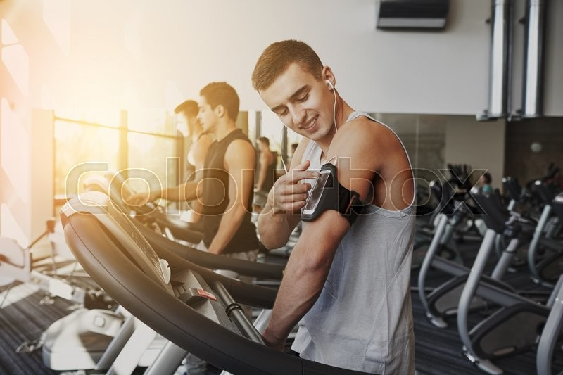 Sport, fitness, lifestyle, technology and people concept - man with smartphone and earphones exercising on treadmill in gym, stock photo