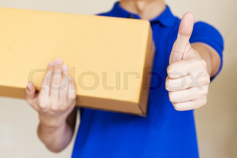Delivery man giving thumbs up as he carries a package isolated on white background (Focus on Hands), stock photo