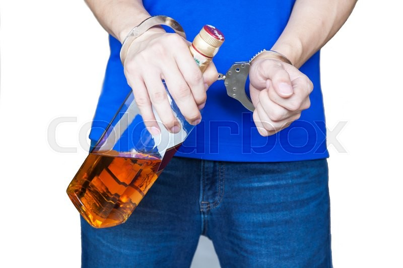Man hand carrying alcohol drink with handcuffs - Drunk driving, alcohol addiction effect concept (Focus on Handcuffs), stock photo