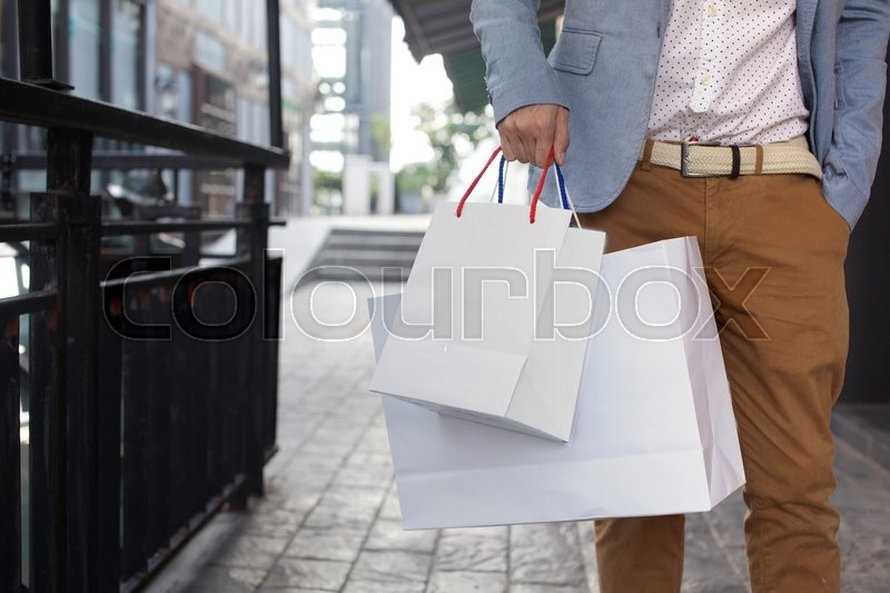 Shopaholic man walking on commercial street with a lot of shopping bags, stock photo