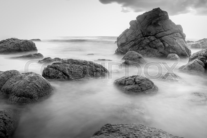 Rock beach in black and white with long exposure photography, stock photo