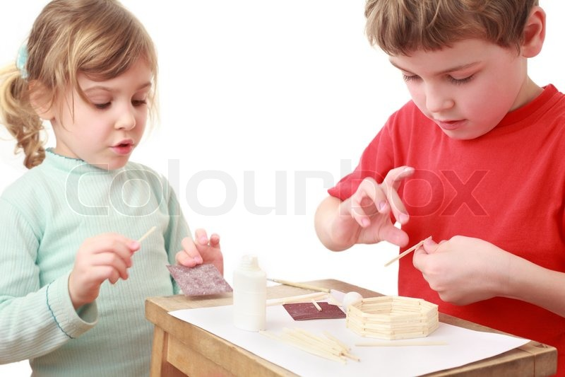 Girl and boy in red t shirt crafts at small table girl talking