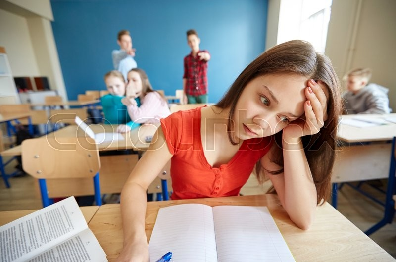 Education, bullying, conflict, social relations and people concept - students teasing and judging girl classmate behind her back at school, stock photo