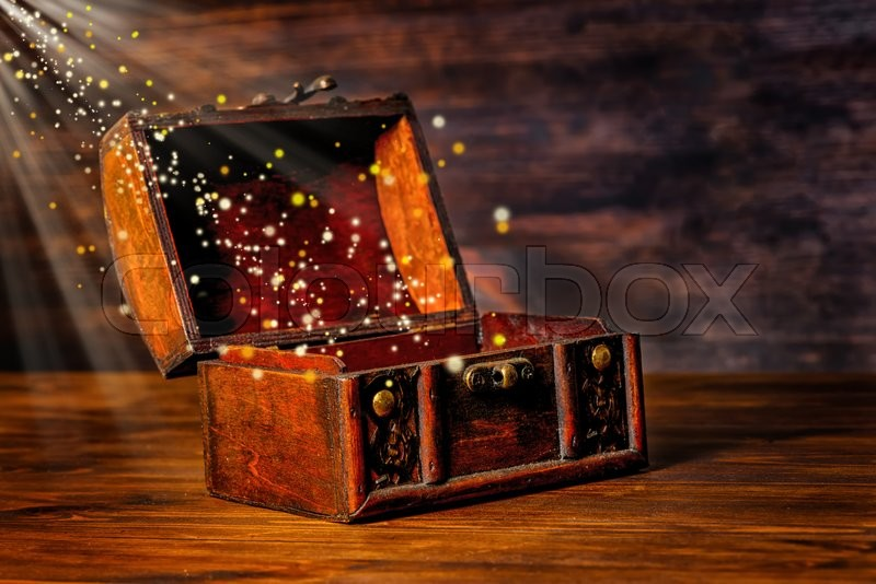 Beautiful greeting card of opened vintage chest treasure with miracle magic light and golden sun beams on wooden background, art design with copy space, close up, stock photo