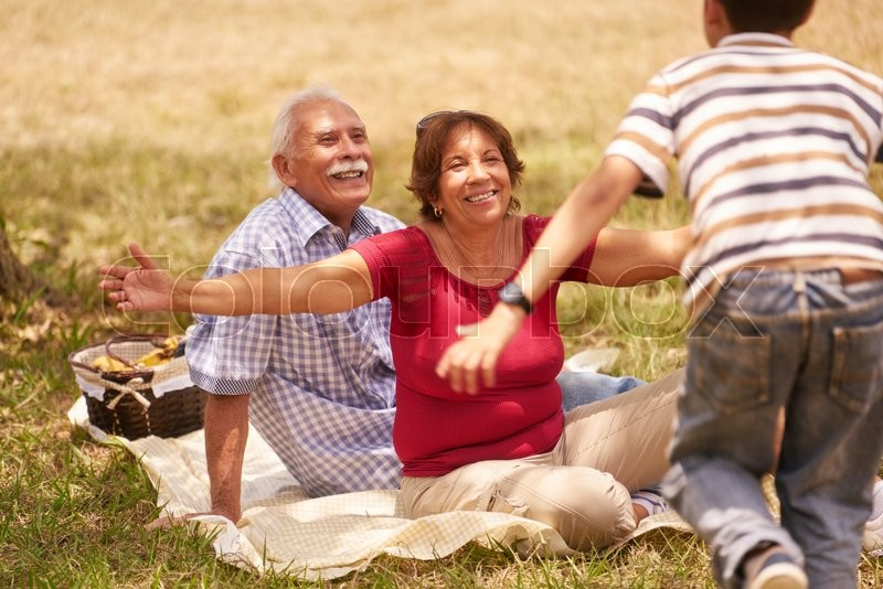 Old people, senior couple, elderly man and woman. Outdoor family having fun with happy grandpa and grandma hugging boy at picnic in park, stock photo