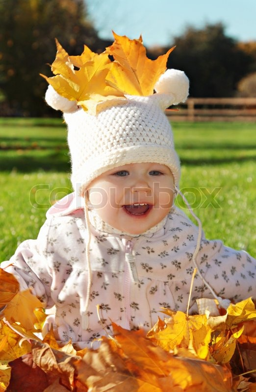 Baby with maple leaf playing in the park, stock photo