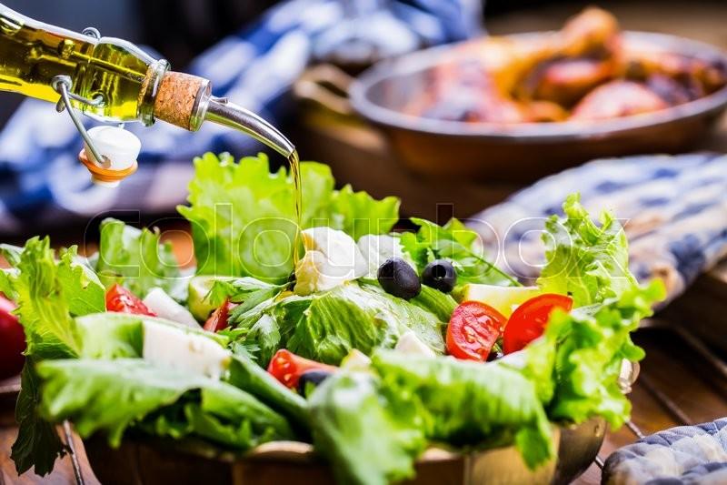 Vegetable lettuce salad. Olive oil pouring into bowl of salad. Italian Mediterranean or Greek cuisine. Vegetarian vegan food, stock photo