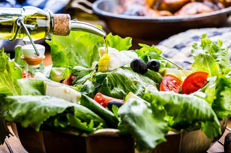 Vegetable lettuce salad. Olive oil pouring into bowl of salad. Italian Mediterranean or Greek cuisine. Vegetarian vegan food, stock photo