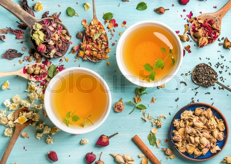 Two cups of healthy herbal tea with mint, cinnamon ,dried rose and camomile flowers in spoons over blue background, top view, stock photo