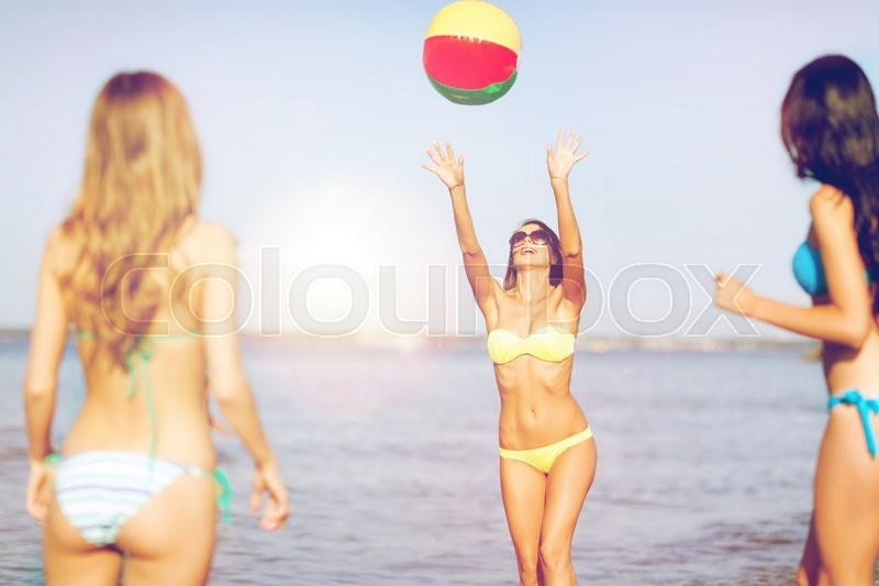 Summer holidays, vacation and beach activities concept - girls in bikinies playing ball on the beach, stock photo