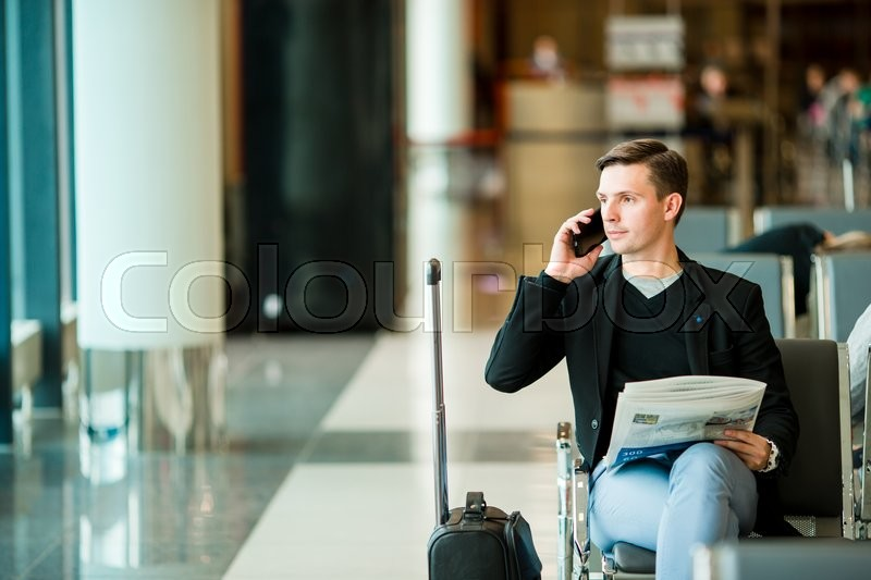 Urban business man talking on smart phone inside in airport. Casual young businessman wearing suit jacket. Handsome male model. Young man with cellphone at the airport while waiting for boarding, stock photo