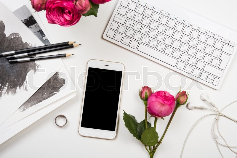Modern smartphone, computer keyboard and fesh pink flowers on white table, freelancer blogger workspace, screen mockup, stock photo