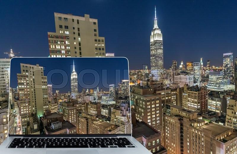 Viewing Manhattan skyline at night on computer screen, stock photo