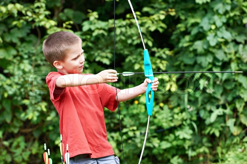 Little archer with bow and arrows outdoors, stock photo