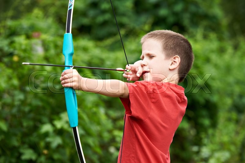 Little archer with bow and arrow outdoors, stock photo