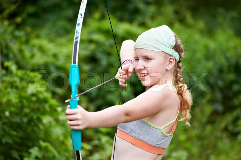 Girl archer with bow and arrow outdoors, stock photo