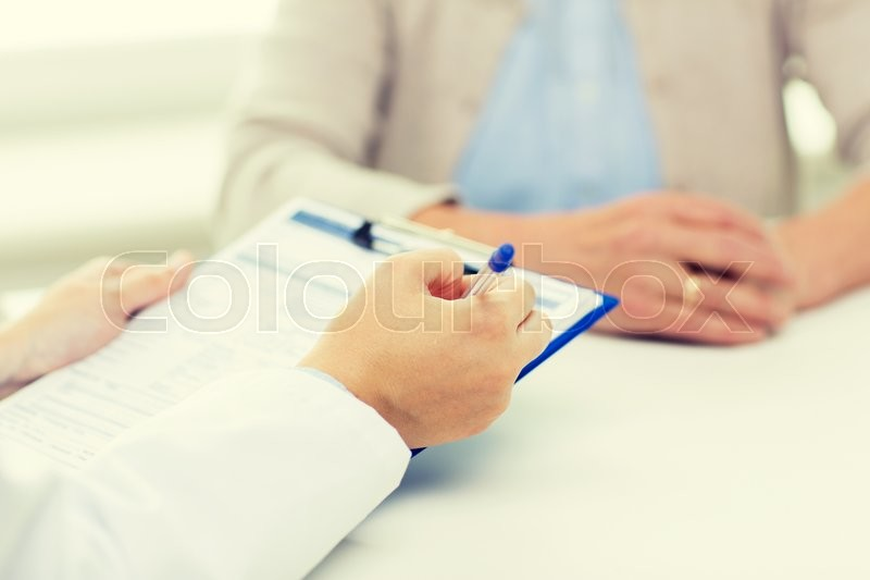 Medicine, age, health care and people concept - close up of senior woman and doctor hands with clipboard meeting in medical office, stock photo