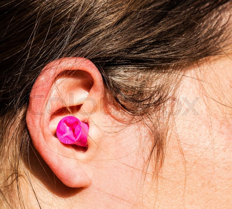 Plugged womans ear for protection, stock photo