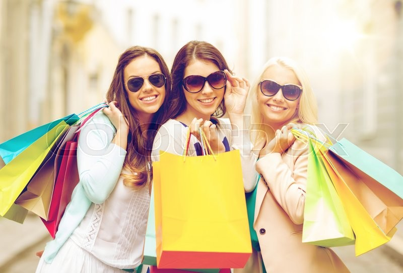 Shopping, sale, happy people and tourism concept - three beautiful girls in sunglasses with shopping bags in ctiy, stock photo