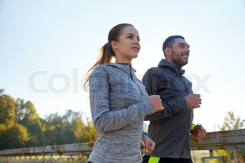 Fitness, sport, people and jogging concept - happy couple running outdoors, stock photo
