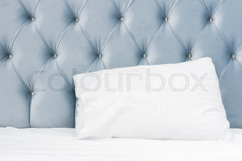 Luxury empty bedroom interior fragment, soft blue headboard, white pillow lays on wide empty bed, stock photo