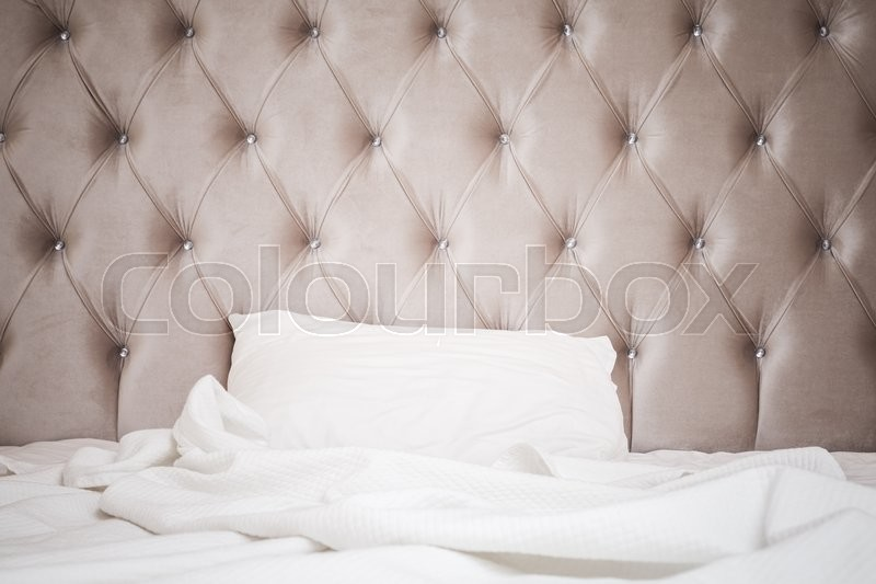 Luxury empty bedroom interior fragment, soft pink headboard, white bedding sheet and pillow lay on wide empty bed, stock photo