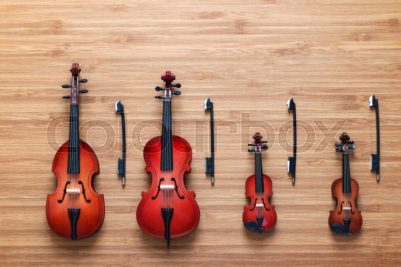 Set of four toy string musical orchestra instruments: violin, cello, contrabass, viola on a wooden background. String Quartet. Music concept, stock photo