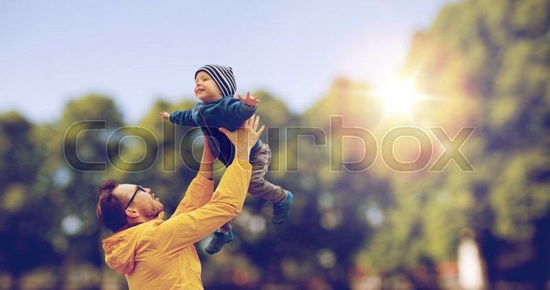 Family, childhood, fatherhood, leisure and people concept - happy father and little son playing and having fun outdoors over summer park background, stock photo