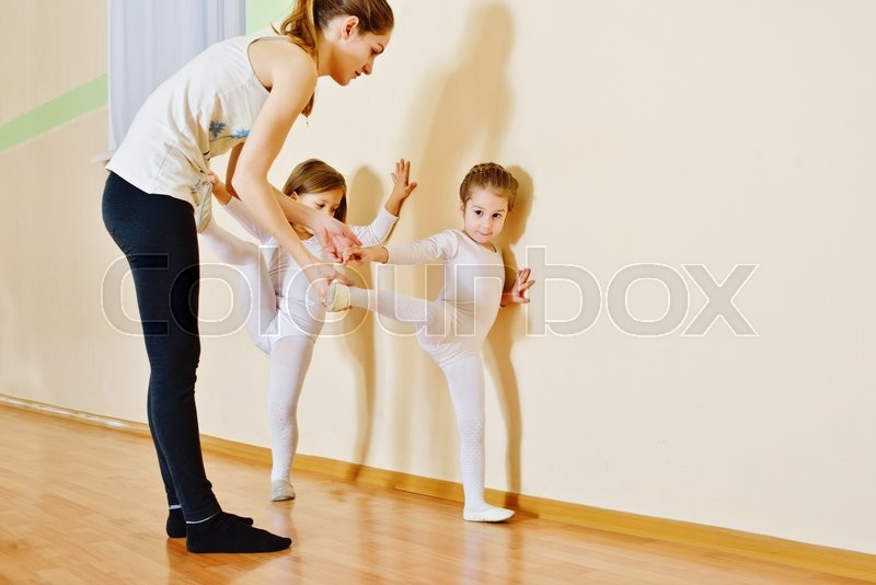 Trainer and two little girls in gymnastic class , stock photo