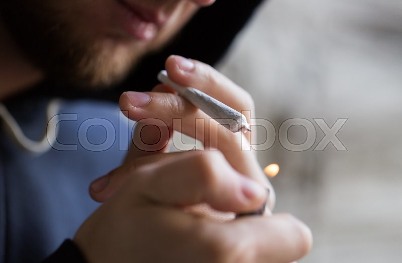 Drug use, substance abuse, addiction, people and smoking concept - close up of addict lighting up marijuana joint with lighter, stock photo