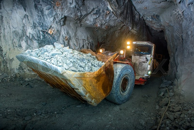 Working inside gold mine tunnel. Gold mining, stock photo