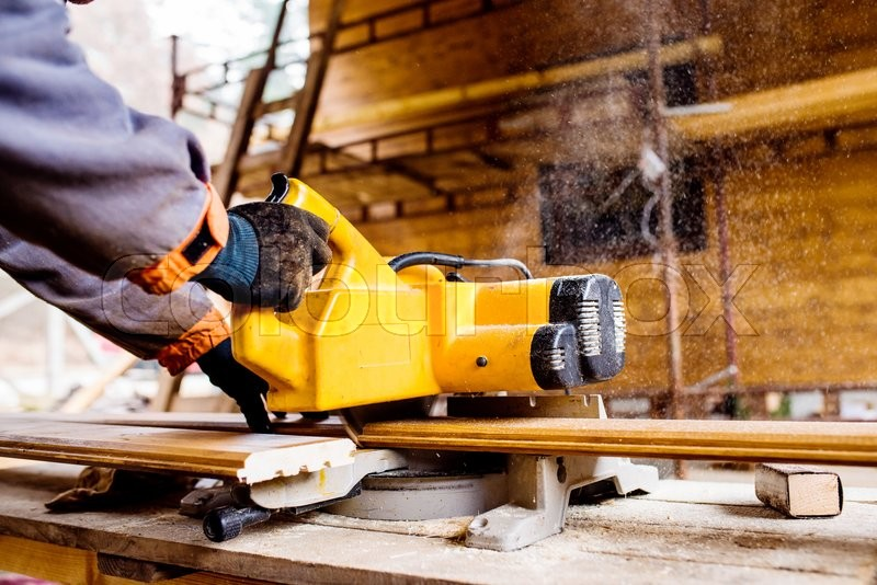 Hands of unrecognizable carpenter working. Man using circular saw to cut planks of wood for home construction, stock photo