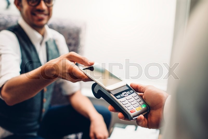 Business man making a contactless smartphone payment, stock photo