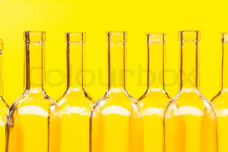Close-up picture of bottle necks with patch of lights against the yellow background, stock photo