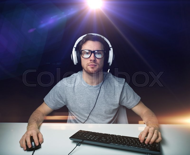 Technology, gaming, entertainment, let\'s play and people concept - young man in headset and eyeglasses with pc computer playing game and streaming playthrough or walkthrough video over light, stock photo