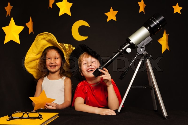Happy five years old kids, boy and girl playing sky watchers stargazing with telescope, stock photo