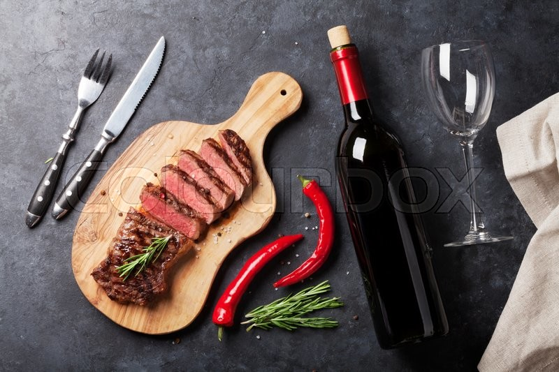 Grilled striploin sliced steak and red wine over stone table. Top view, stock photo