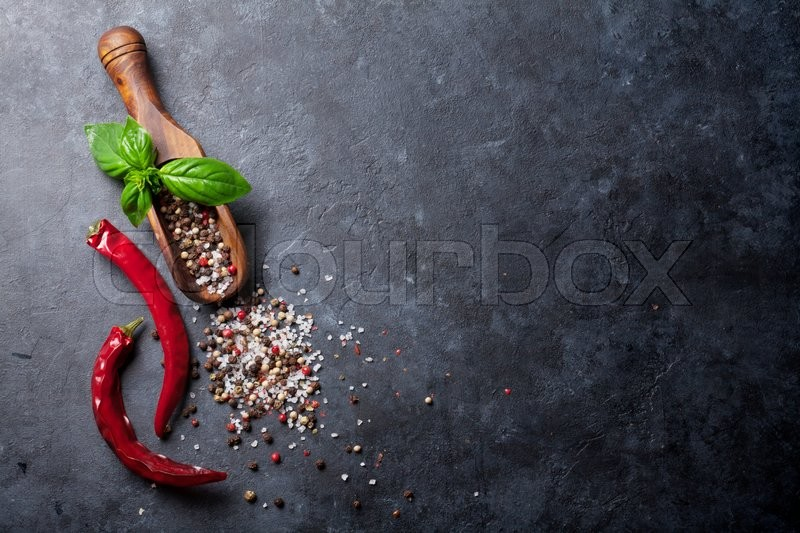 Pepper and salt spices, basil herb and chili pepper. Red, white and black peppercorn. On dark stone table. Top view with copy space, stock photo